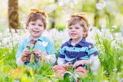 Dois rapazes pequenos que vestem as orelhas do coelhinho da Páscoa e que comem o chocolate Imagens de Stock
