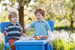 Dois rapazes pequenos que vestem as orelhas do coelhinho da Páscoa, ovo colorido de pintura Fotografia de Stock Royalty Free