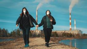 Dois residentes de uma cidade industrial, um homem e uma mulher, corrida nos respiradores ao longo de uma estrada de terra ao lon filme