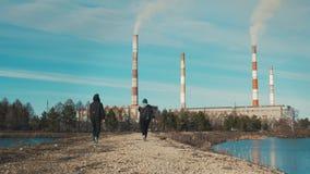 Dois residentes de uma cidade industrial, um homem e uma mulher, estão andando ao longo de uma estrada de terra vídeos de arquivo