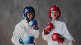 Dois resolutos e indivíduos agressivos no capacete da defesa e olhares das luvas da caixa da luta na câmera e pronto para a ação  filme