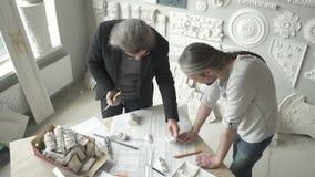 Dois restauradores dos arquitetos estão funcionando com o projeto criativo que está no escritório brilhante video estoque