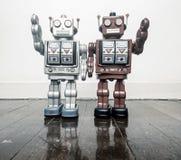 Dois robôs do vintage dizem olá! em um assoalho de madeira tonificado imagens de stock royalty free