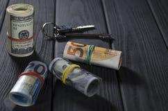 Dois rolos de contas de cem-dólar, um rolo do cinqüênta-rolo, um rolo de vinte-Euro amarrado com elásticos em uma tabela de madei foto de stock