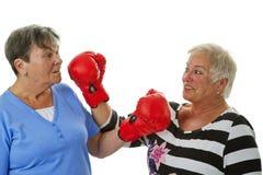 Dois sêniores fêmeas com a luva de encaixotamento vermelha Imagens de Stock Royalty Free