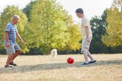 Dois sêniores que jogam o futebol no parque Fotografia de Stock