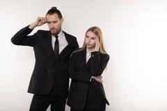 Dois sócios comerciais em ternos pretos, homem farpado considerável e mulher loura bonita pensando sobre a resolução imagem de stock