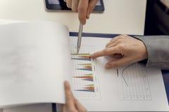 Dois sócios comerciais que apontam no gráfico de negócio Representat imagem de stock