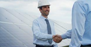Dois sócios do perito técnico nos painéis fotovoltaicos solares, controlo a distância executam operações rotineiras para monitora fotografia de stock