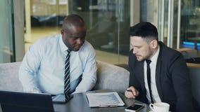 Dois sócios multi-étnicos na roupa formal que senta e que discute detalhes financeiros das cartas ao olhar o bloco de notas dentr filme
