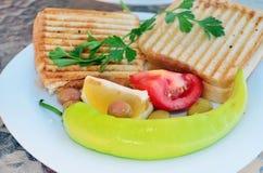 Dois sanduíches do brinde com tomate e pimentas em uma placa branca Fotografia de Stock Royalty Free