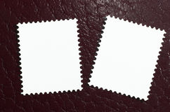 Dois selos em branco em um fundo de couro vermelho fotos de stock