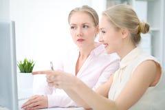 Dois senhoras ou colegas do negócio que discutem algo no fundo do escritório Foto de Stock