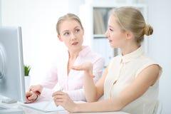 Dois senhoras ou colegas do negócio que discutem algo no fundo do escritório Imagem de Stock Royalty Free