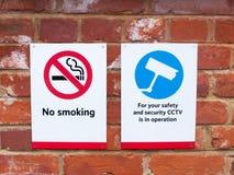 dois sinais no cctv do estação de caminhos-de-ferro não fumadores Fotos de Stock