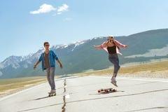 Dois skateres felizes que longboarding na estrada reta Fotos de Stock