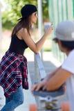 Dois skateres que usam o telefone celular na rua Fotos de Stock Royalty Free