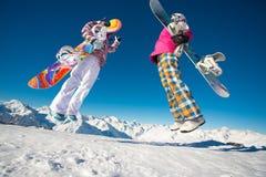 Dois snowboarders das amigas que saltam nas montanhas alpinas Fotografia de Stock