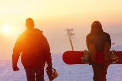 Dois snowboarders que andam contra o céu do por do sol Fotos de Stock