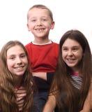 Dois sorrisos dos adolescentes e do rapaz pequeno Fotos de Stock Royalty Free