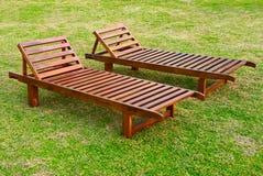 Dois sunbeds de madeira no gramado da grama verde Fotografia de Stock