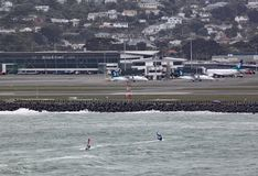 Dois surfistas do vento na baía de Lyall em Wellington New Zealand em um dia tormentoso cinzento O aeroporto pode ser visto no fu foto de stock