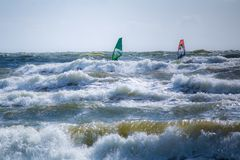 Dois surfistas no mar Báltico tormentoso em Lituânia imagens de stock