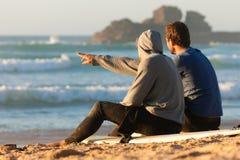 Dois surfistas que falam na praia Fotos de Stock Royalty Free