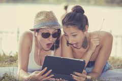 Dois surpreenderam as meninas que olham a almofada que discute a notícia a mais atrasada da bisbolhetice Foto de Stock