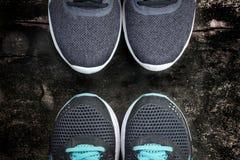 Dois tênis de corrida dos pares em um assoalho de madeira sujo Imagem de Stock