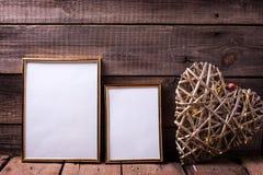 Dois tamanhos dourados vazios do differenr dos quadros e coração decorativo w Imagens de Stock