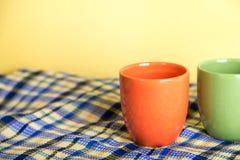 Dois tampões verdes e posição alaranjada em uma toalha azul do waffle em um fundo amarelo Fotografia de Stock Royalty Free