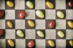 Dois tipos de tomates de cerejas maduros coloridos em um tabuleiro de xadrez, vista superior Fundo do vintage Conceito do aliment Imagem de Stock