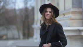 Dois tiros da moça glamoroso elegante com o cabelo longo, o chapéu roxo e as caminhadas pretas do revestimento olhando à câmera F video estoque