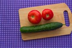 Dois tomates e um pepino em uma placa de madeira em um fundo roxo Foto de Stock Royalty Free