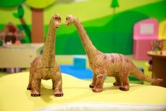 Dois Toy Dinosaurs Talking Happily no campo de jogos do ` s das crianças imagem de stock