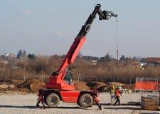 Dois trabalhadores com um carregador telescópico do alimentador montam lajes de cimento para a construção nova imagens de stock