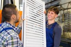 Dois trabalhadores cuidadosos que inspecionam janelas Fotografia de Stock Royalty Free