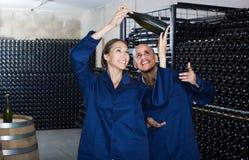 Dois trabalhadores da adega que guardam a garrafa do vinho Imagens de Stock Royalty Free