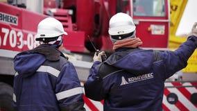 Dois trabalhadores da construção no unifrorm e os capacetes estão para trás à câmera e à conversa filme