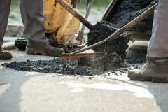 Dois trabalhadores da construção que remendam a colisão na estrada fotografia de stock royalty free