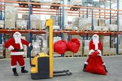 Dois trabalhadores das cláusulas de Santa no trabalho no grande depósito imagem de stock