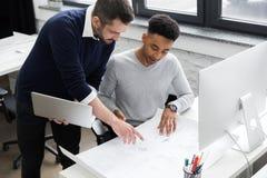 Dois trabalhadores de escritório masculinos de sorriso que trabalham com portátil Foto de Stock