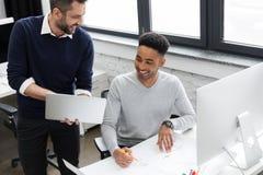 Dois trabalhadores de escritório masculinos de sorriso que trabalham com portátil Imagens de Stock