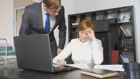 Dois trabalhadores de escritório sentam-se na mesa, uma mulher estão trabalhando no computador, um homem estão próximo Estão rind fotografia de stock royalty free