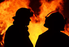Dois trabalhadores de salvamento dos homens do bombeiro na chama da noite imagem de stock royalty free