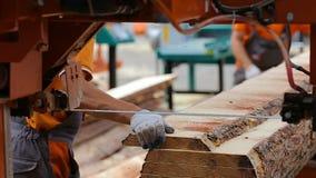 Dois trabalhadores descarregam placas das serrações na pilha filme