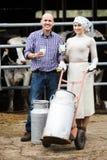 Dois trabalhadores do fazendeiro no estábulo Fotografia de Stock Royalty Free