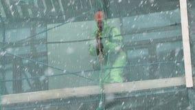 Dois trabalhadores dos homens estão no andaime da construção e levantam pranchas de madeira vídeos de arquivo