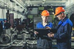 Dois trabalhadores em uma planta industrial com uma tabuleta à disposição, workin imagem de stock royalty free